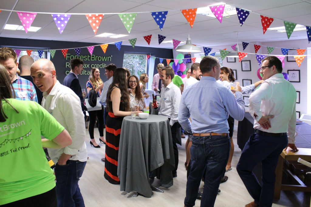 People networking at party with bunting and gin