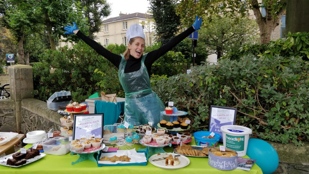 Woman surrounded by cakes at charity bake sale